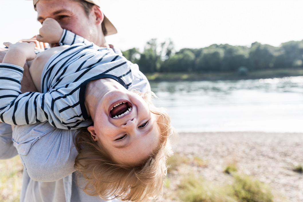 Lachendes Kind spielt mit Vater