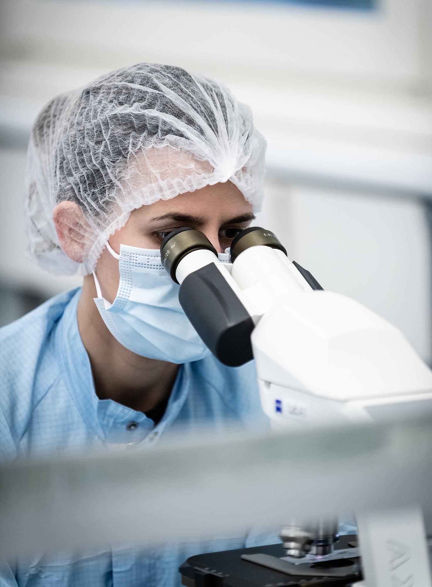 Laborantin schaut durch ein Mikroskop