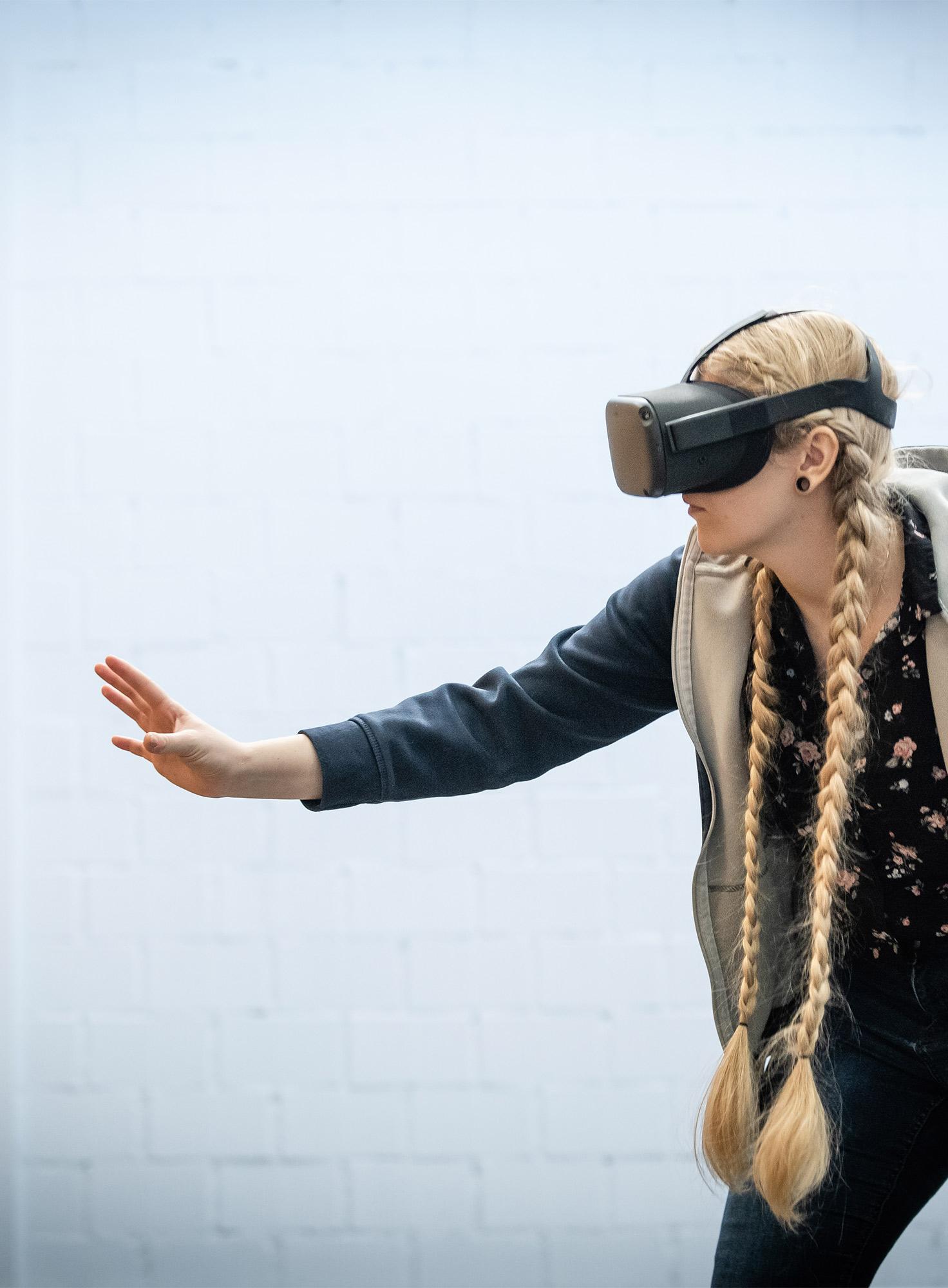 Frau mit VR-Brille tastet sich voran