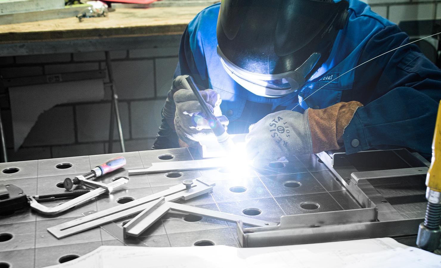 Ein Mitarbeiter mit Schutzhelm beleuchtet ein Bauteil auf der Montagebank